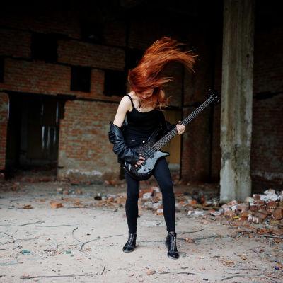 Svartklädd kvinna spelar gitarr och slänger med håret.