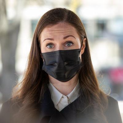 Statminister Sanna Marin iförd mask under en intervju utomhus.