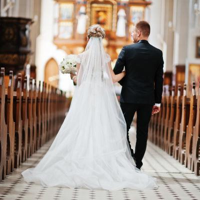 Ett brudpar går med ryggen till kameran längs mittgången i en kyrka.