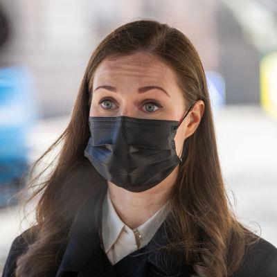 Närbild av brunhårig kvinna med svart munskydd. Statsminister Sanna Marin 31.3.2021.