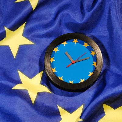 Bild föreställande en klocka med EU:s flagga i bakgrunden.
