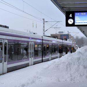 Snöhög på tågstation, invid tåg som står stilla.