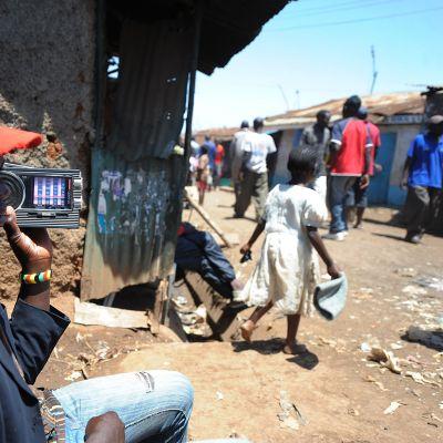En kenyansk man lyssnar till nyheter om valet på en radio