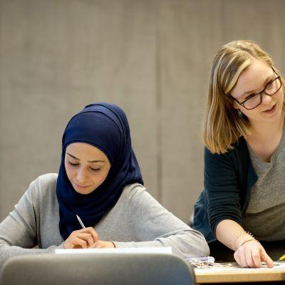 Potsdamin yliopistolla on käynnissä ensimmäinen pakolaisille tarkoitettu opettajakurssi. Kuvassa opettaja Claudia Hubatsch neuvoo Nouria ja Yaseria, jotka haluavat työskennellä opettajina Saksassa.
