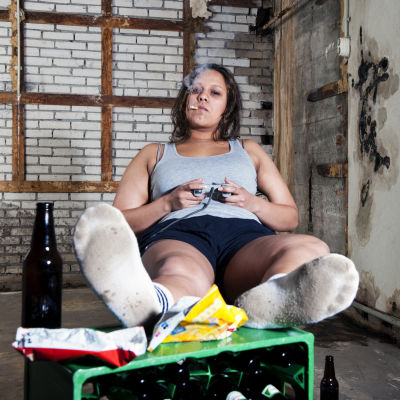 kvinna klädd i smutsiga kläder röker och spelar tv-spel