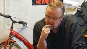 Professori ja pappismunkki Serafim Seppälä työhuoneessaan Joensuussa polkupyöränsä kanssa.