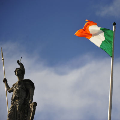 Irlands flagga i orange, vitt och grönt framför en gammal staty i Dublin.