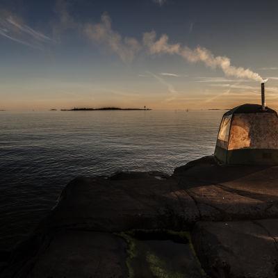Ett bastutält på en klippa vid havet i solnedgång.
