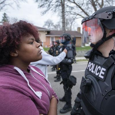 En kvinna med mörkröd munkjacka står mot en kravallpolis under en protest i Brooklyn Center på söndagen.
