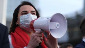 Svetlana Tichanovskaja talar i en megafon. Hon har munskydd på sig och en röd halsduk runt halsen.