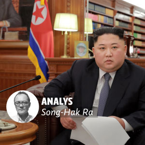 Kim Jong-Un sitter med en pappersbunt i handen.