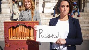 Nainen näyttää katusoittajan edessä kameralle lappua, jossa lukee Révolution!