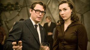 Kuvassa Fredrik Nyman (Per Kjerstad) ja Anna (Anne Regine Ellingsæter) seisovat ja katsovat jotakin epäillen.