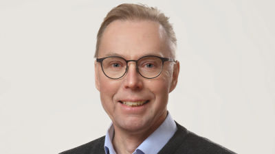Porträttfotografi av man i medelåldern, mannen har kort brunt hår och glasögon.