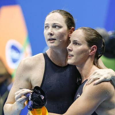 Två simmarsystrar håller om varandra och väntar spänt på resultat.