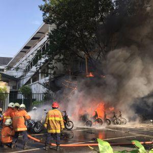 Brandmän släcker branden utanför polishögkvarteret i Surabaya efter självmordsattacken där.