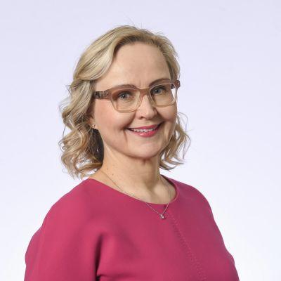 En kvinna med blont lockigt hår och glasögon. Hon ler mot kameran.