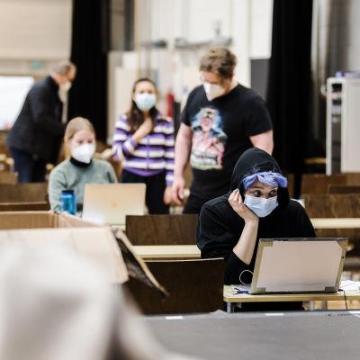 Personer i munskydd under studentskrivningar i Helsingfors i mars 2021.