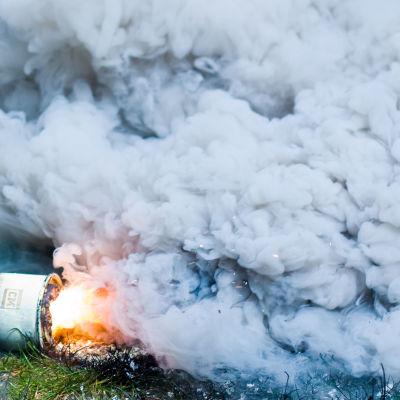 En rökgranat på en gräsmatta varifrån det kommer tjock, grå rök.
