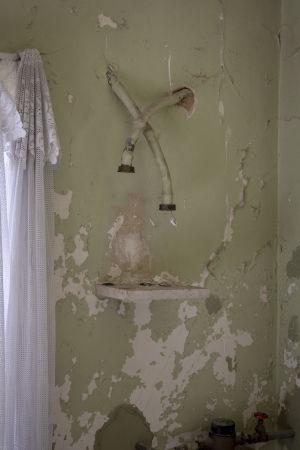 En bild föreställande en vägg i Maria Neves lägenhet. Målfärgen har flagnat vilket visar på behovet av att renovera lägenheten.
