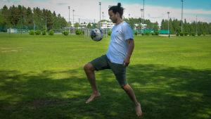 Mies pomputtaa jalkapalloa polvellaan