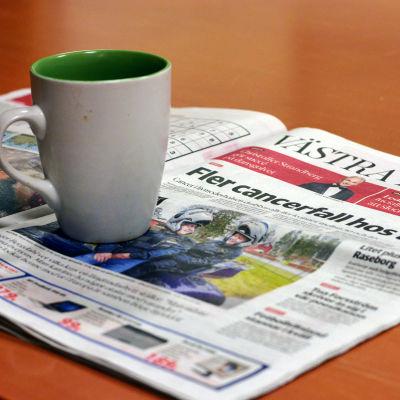 En kaffemugg placerad på en dagstidning.