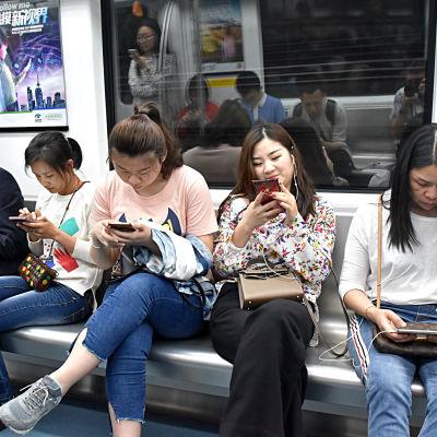 Kineser surfar på mobiltelefonen i ett tåg