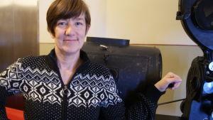 Camilla Roos poserar vid en gammal kamera på Bio Savoy i Mariehamn.