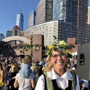 Sveriges generalkonsul Annika Rembe på midsommarfest i skånsk folkdräkt och blommor i håret i New York.