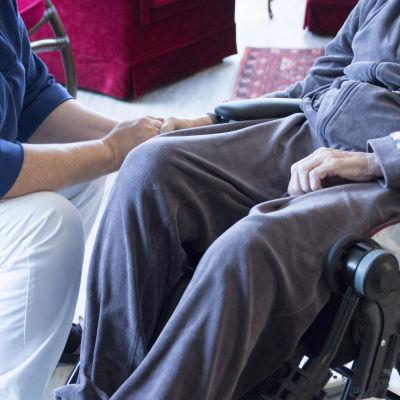 En skötare håller en äldre persons hand. Den äldre personen sitter i rullstol.