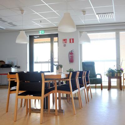 Ett rum som är möblerat med ett matbord och två fåtöljer.