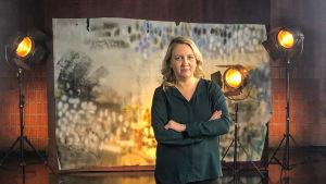 Elli Toivoniemi seisoo studiossa taustalavasteen ja studiolamppujen edessä. Kuva otettu lyhytvideosarjaan Me elokuvantekijät.