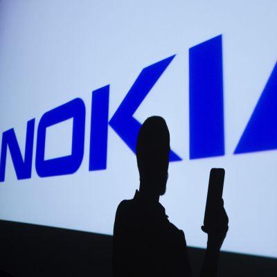 Nokias logo i bakgrunden. I förgrunden syns en person som håller i en telefon.