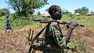En rebell från den kristna rebellgruppen Herrens motståndsarmé står med ett vapen på axeln.