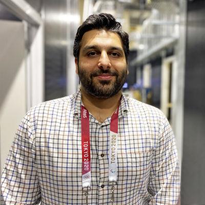 Ali Al-Naama ser in i kameran. Han är iklädd rutig skjorta.