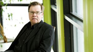 Yle Asian vastaava tuottaja Timo Järvi istuu tuolissa.