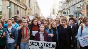 """På bilden syns klimataktivisten Greta Thunberg med sin kända skylt """"Skolstrejk för klimatet"""" gå sida vid sida med massor av unga klimataktivister i Paris i september 2019."""