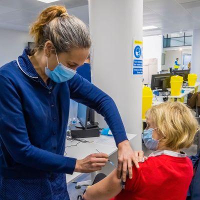 En kvinna vaccineras mot covid-19 i England.