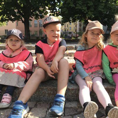 Fyra dagisbarn sitter ute på en trappa.
