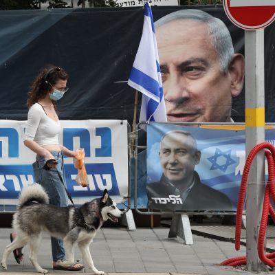 En kvinna med munskydd vandrar i Jerusalem förbi valaffischer föreställande Benjamin Netanyahu.