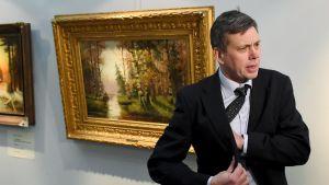 Kriminalkomissarie Juha Siljamäki berättar om en omfattande konstförfalskningshärva. I bakgrunden beslagtagna målningar.
