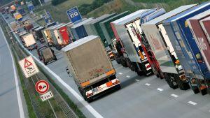 Lastbiler i kö på Autobahn i Tyskland
