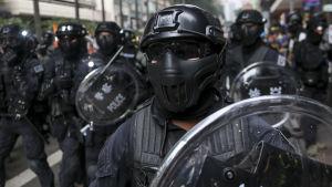 Kravallpolis marcherar mot demonstranter i Hongkong på söndagen.