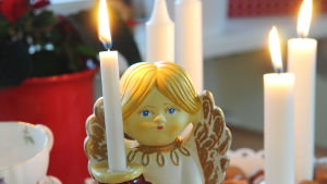 Luciafigur i porslin håller ett levande ljus.