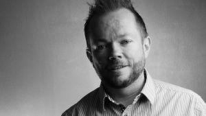 En svartvit bild av Per Axbom som ler litegrann.
