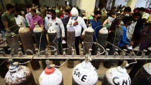 Invånare som fyller på syrgastuber i staden Allahabad på en syrgasstation