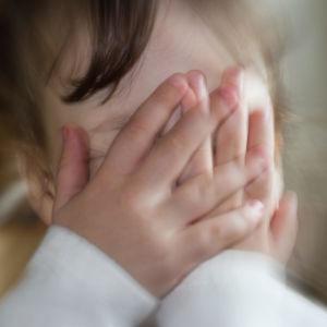 Litet barn täcker ansiktet med händerna. Illustrerande bild.