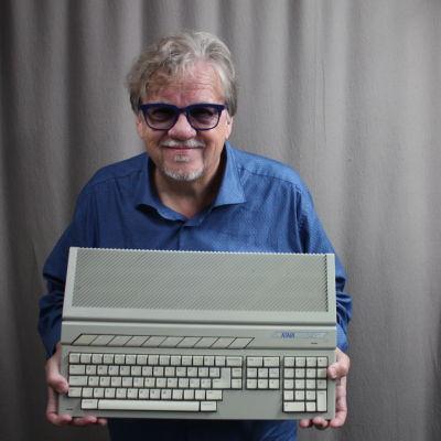 Mikko Alatalo hymyilee kameralle ja esittelee vanhaa Atari tietokonetta.