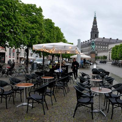 Tom uteservering på Højbro Plads i Köpenhamn med Christiansborg slott i bakgrunden.