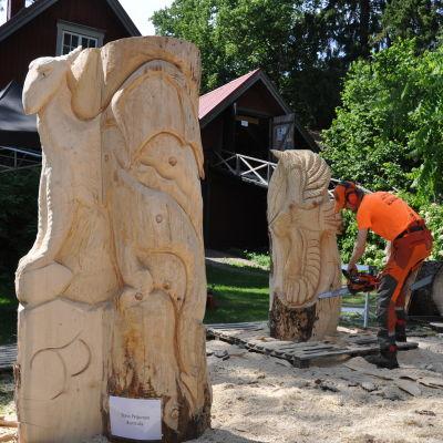 Timo Peiponen veistää puuveistosta moottorisahalla. Kuvan etuosassa näkyy suuri puuveistos.